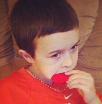 Child chewing on SentioCHEWS Red Soccer Ball could be part of his Sensory Diet