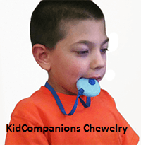 Boy with chewy fidget in mouth - Our KidCompanions Chewelry, chewable jewelry, is made in Canada in a medical device manufacturing facility that is ISO certified. Parents can rest assured they are buying a SAFE chewy and fidget!